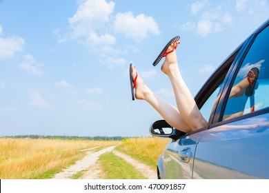 female legs dangling from the open car window in the shales