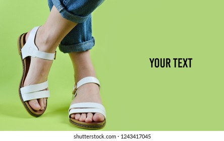 Female legs dressed in jeans and shod in sandals posing isolated on geen background. Women's fashion. Women's summer footwear. Copy space.