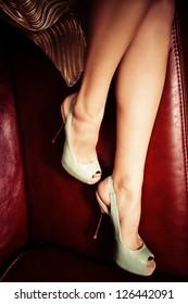 female legs in elegant high heel shoes on leather sofa