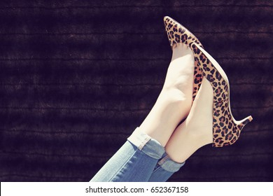 Female legs with feet in the air wearing leopard print high heels and blue jeans.