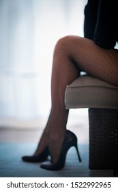 female legs in fishnet tights in high-heeled shoes sitting on a sofa in front of a window with a white curtain