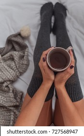 female legs in gray leggings, a cup of coffee, a concept, a top view