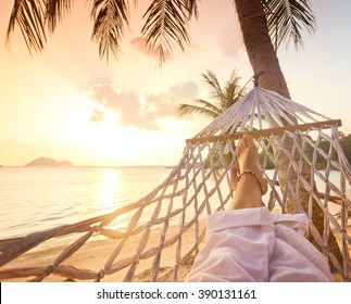 Female legs in a hammock on a background of the sea, palm trees and sunset. Vacation concept, point of view