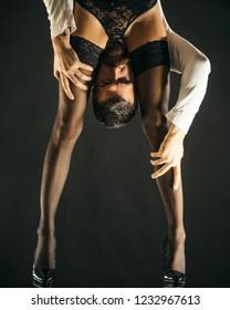 Female legs in high heel black shoes and fishnet stockings. Sexy man hugs beautiful legs woman. Woman in black lace lingerie and stockings in beautiful legs. Attractive female body in lace lingerie