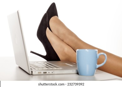 female legs in the high heels, on a table with a laptop