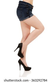 Female legs in jeans and high heel shoes.