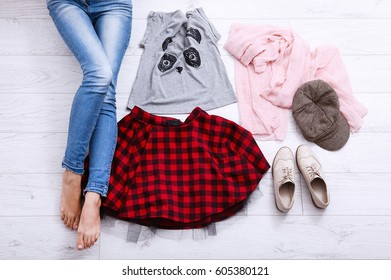 Female legs in jeans near fashion clothes on white wooden background. Top view and copy space. Spring outfit