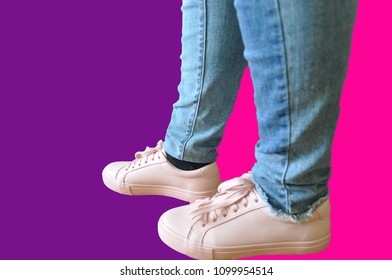Female legs in jeans and sneakers of the color of a dusty rose on a bright background in the style of pop art purple and crimson shades. Summer hipster vibes style.