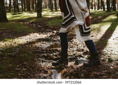 Female legs jumping into the puddle in the sunny forest. Horizontal outdoors shot.