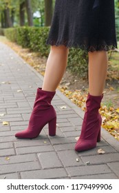 Female legs in knitted warm dress and velvet boots