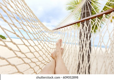 Female legs laying relaxed on hammock on tropical beach.