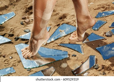 Female legs and mirror shards on the sand