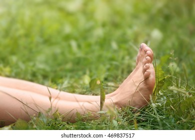 Female legs on green grass