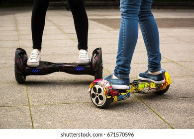 Female legs on hoverboards close-up. Two girls go on hoverboards.