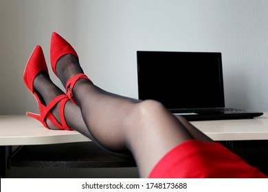 Female legs on office table with laptop, hot woman in black stockings and red shoes on high heels sitting at the desk. Concept of seductive secretary, female fashion, relax at work