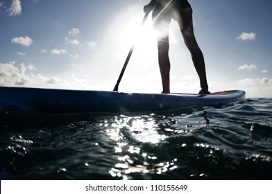 Female legs on paddleboard.
