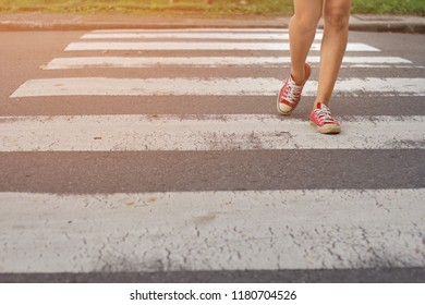 Female legs on the pedestrian crossing. Woman crossing the street at a crosswalk,Soft focus.