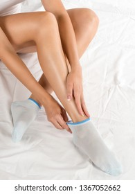 Female legs in pale blue short socks. Woman sitting on white bedding and touch her feet by hands. Classic manicure. Skin care, depilation, home, self love, spa, feminity, hosiery and trendy footwear