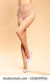 Female legs in pantyhose and high heels
