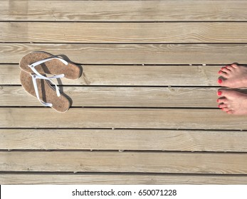 Female legs with a pedicure and sandals on the beach path of boards