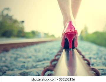 Female legs in red high heels on the rail of the railway. (Vintage style)
