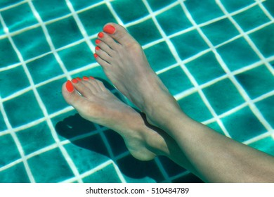 Female legs with red nail polish, soaked in the sunlit water of a pool during summer vacation.