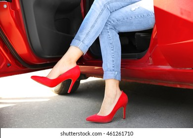 Female legs in red shoes from opened car door