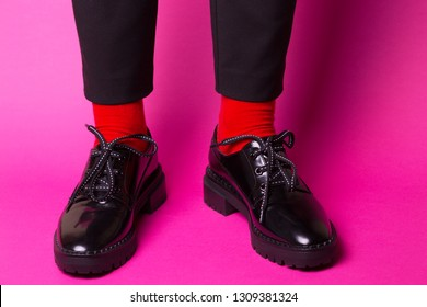 female legs in red socks and stylish black shoes on a pink background. fashion trends. beautiful female shoes
