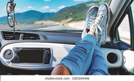 Female legs in ripped jeans and blue sneakers inside car with mountains landscape at background. Woman relaxing during road trip