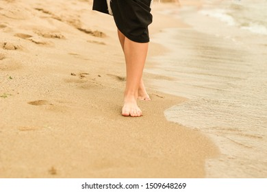 Female legs in the sand. Human foot. Sea. Advertising