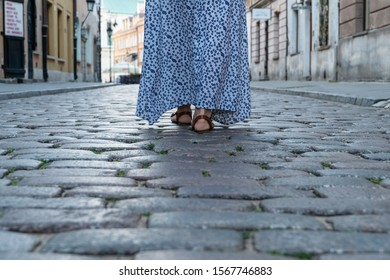 Female legs in sandals walk on the cobblestones on a city street