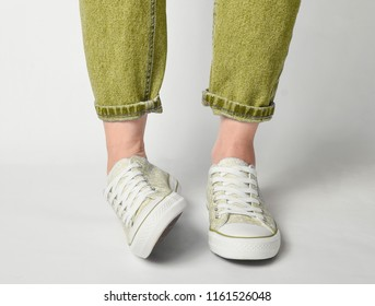 Female legs in short jeans and sneakers stand on a white background