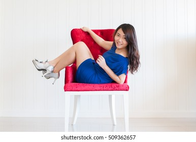 Female legs with silver high heels on red sofa.