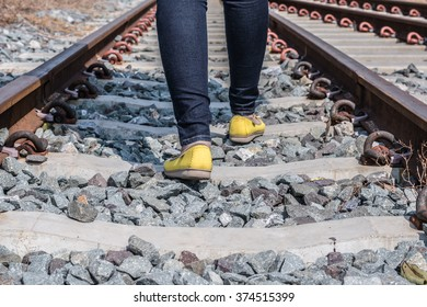 female legs in sneakers on the rail of the railway