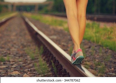 Female legs in sneakers on the railway tracks on a summer day