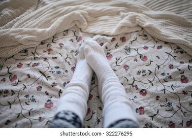 female legs in socks in bed