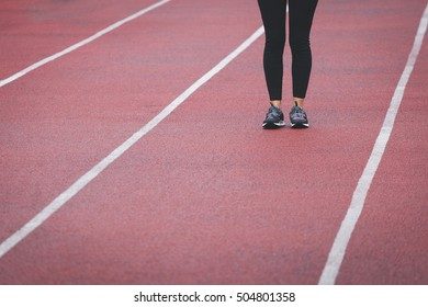 Female legs in sport sneakers on the track