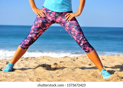 Female legs in sport style clothes on the beach