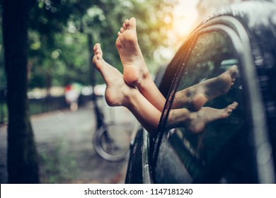 Female legs stick out of the car window. Woman having fun and relaxing in a car drung road trip.