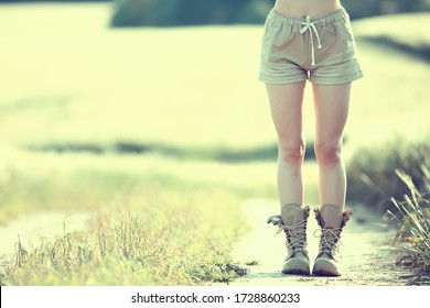 female legs in summer trekking boots / walks anonymously on the field woman big shoes girl