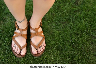 Female legs with tattoos on green grass