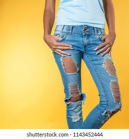 Female legs in torn jeans on an orange background