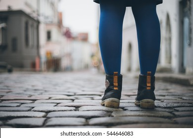 Female legs in trendy boots on cobblestone pavement, from ground back view