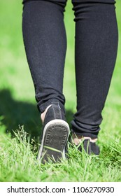 Female legs walking on green grass, rear view, black jeans and light moccasins