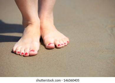Female legs walking in water, girl's barefoot legs on the sand beach