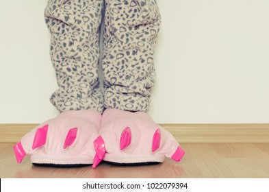 Female legs in warm pajama and cute pink monster foot slippers with big claws. Bedtime and good morning concept.