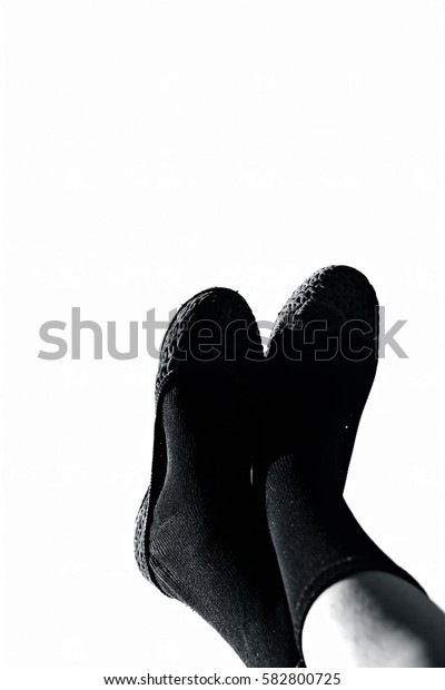 Female legs wearing black socks isolated on white.