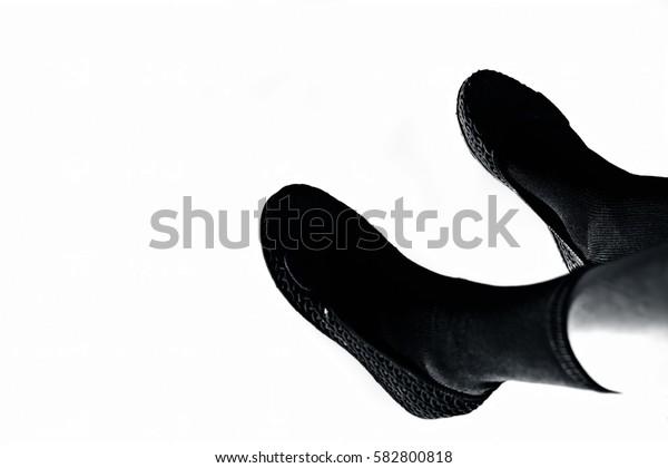 Female legs wearing black socks isolated on white.