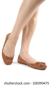 Female legs wearing  brown moccasin flat shoes over white background