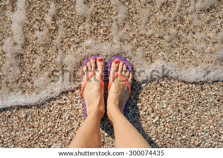Female legs wearing flip flops near sea. top view